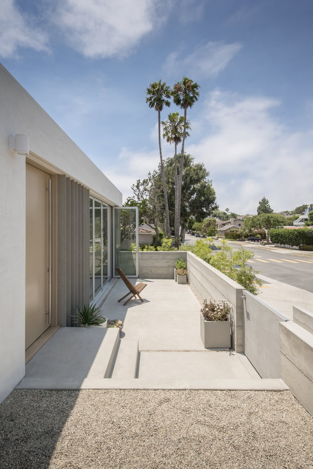 Outdoor, Front Yard, Small Patio, Porch, Deck, Raised Planters, Concrete Patio, Porch, Deck, and Horizontal Fences, Wall On the sides of the front folding glass doors are vertical cement board fins that emphasize the street-side corner.     Best Photos from A Cramped Midcentury Bungalow Gets a Luminous New Addition
