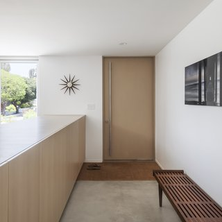 A wood pivot door with a recessed, custom-cut coir doormat.