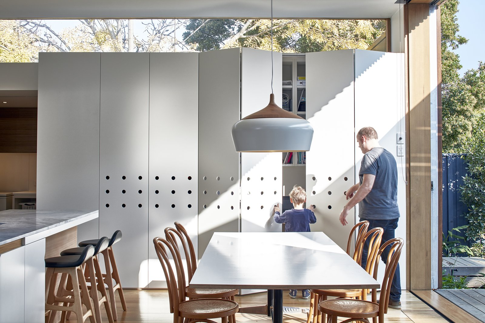 Dining Room, Pendant Lighting, Table, Chair, Light Hardwood Floor, Storage, and Stools The walls, ceilings, windows, and cabinetry were all strategically positioned to unveil views to the outdoors.   Best Photos from Wooden Screens Shade This Sustainable Melbourne Residence