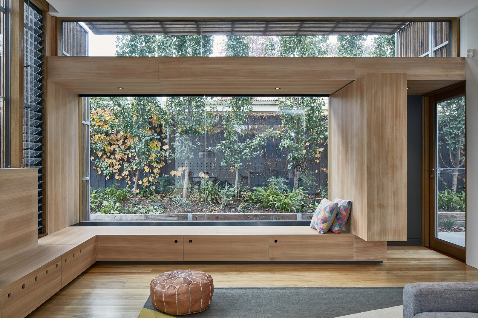 Living Room, Light Hardwood Floor, Recessed Lighting, Bench, Sofa, and Rug Floor Upon entering the house, one immediately sees right through to the rear garden from the main corridor.  Best Photos from Wooden Screens Shade This Sustainable Melbourne Residence
