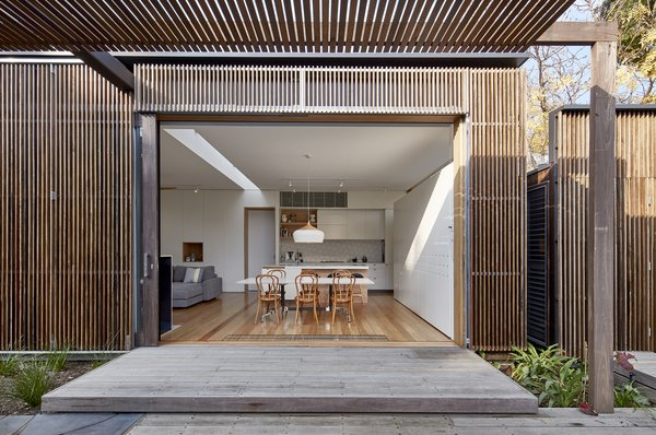 The addition has a skin of hardwood screens that offer protection from sunlight arriving from the north and west. The screens provide shade and privacy while still revealing views of the outdoor area and the pool.