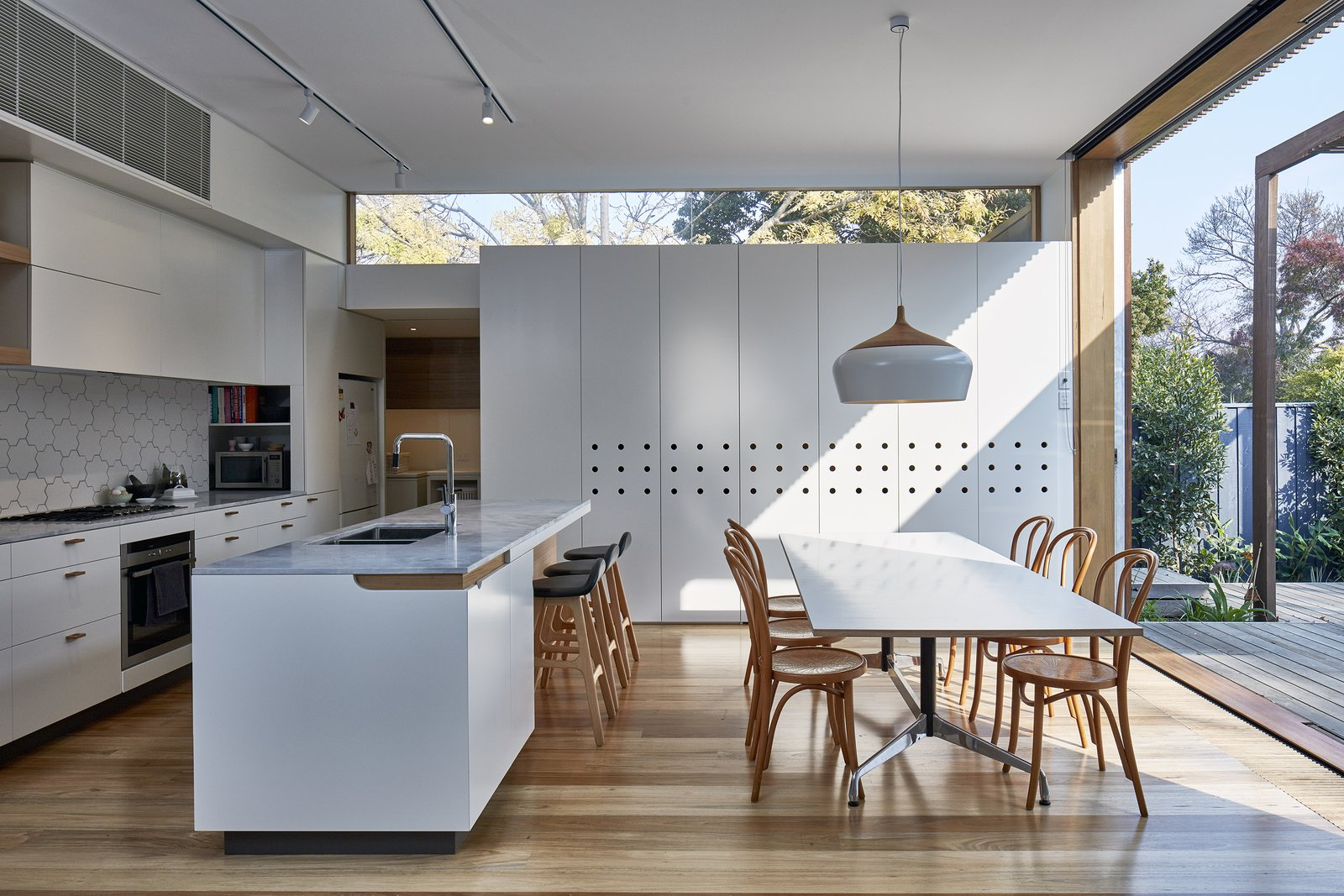Dining Room, Track Lighting, Pendant Lighting, Chair, Table, Light Hardwood Floor, and Stools Plenty of white finishes give the interiors a clean, bright look.  Photos from Wooden Screens Shade This Sustainable Melbourne Residence