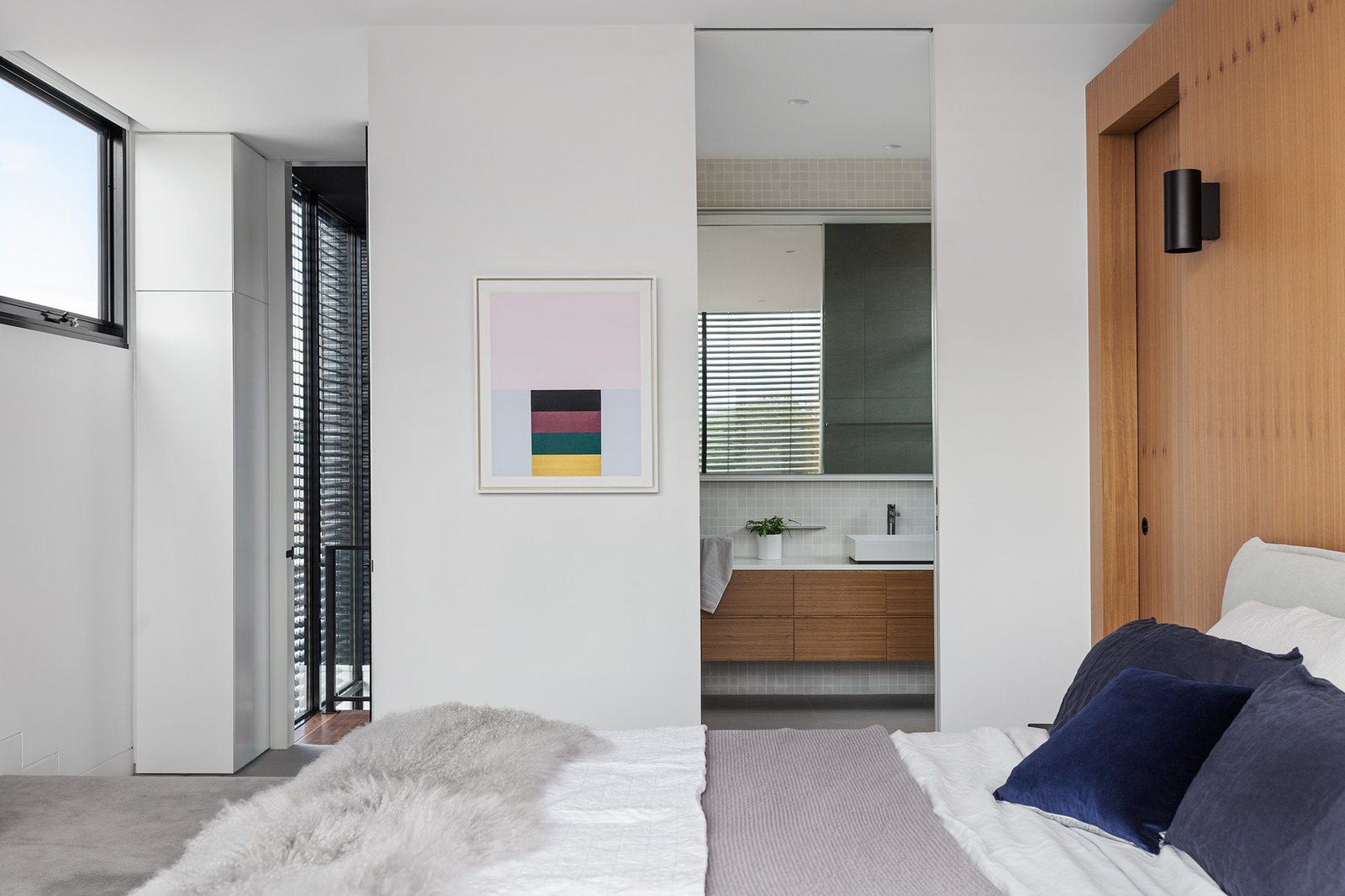 Bedroom, Wall Lighting, Concrete Floor, and Bed The windows are clad with exterior, motorized venetian blinds that provide some welcome shade.   Best Photos from A Sleek Australian Dwelling Keeps its Cool With Passive Design