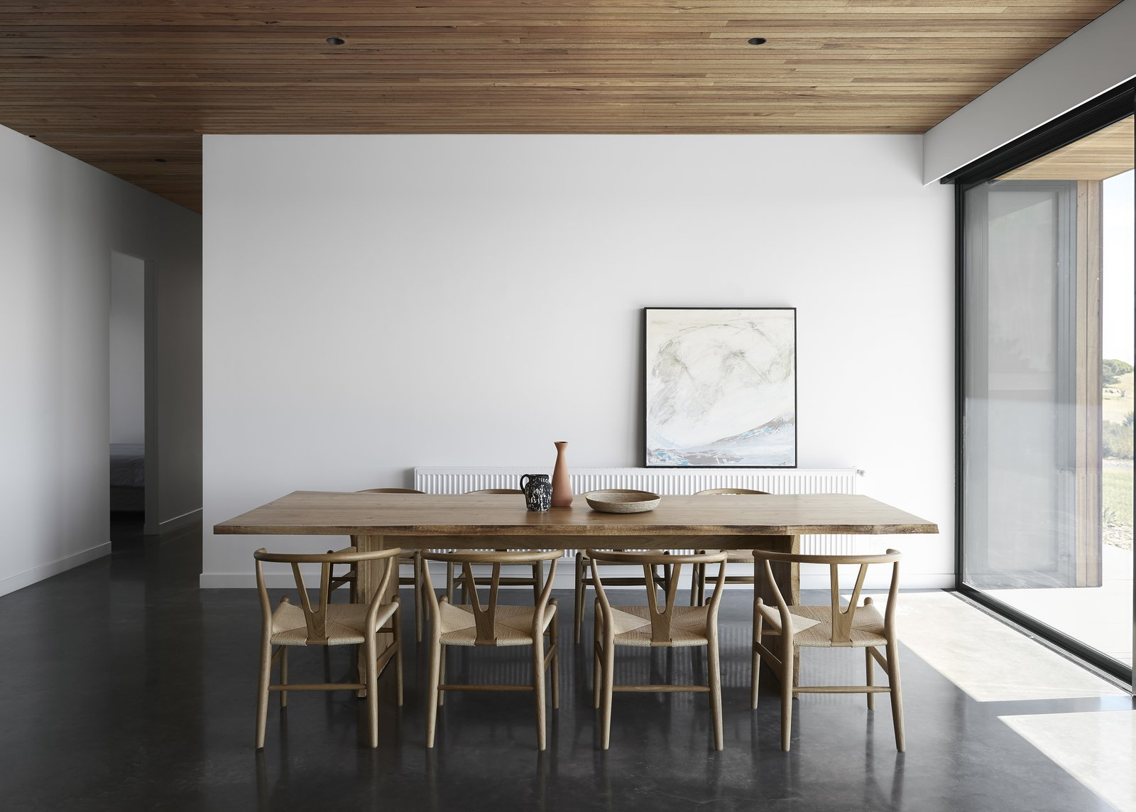 Dining Room, Table, Concrete Floor, Chair, and Recessed Lighting The house has floors of burnished concrete, providing thermal mass in the cooler months. The cement retains heat from the sun during the day and then slowly releases it back into the atmosphere to warm the interiors in the evening.     Photo 6 of 10 in Two Timber-Clad Pavilions Make Up This Australian Family Retreat