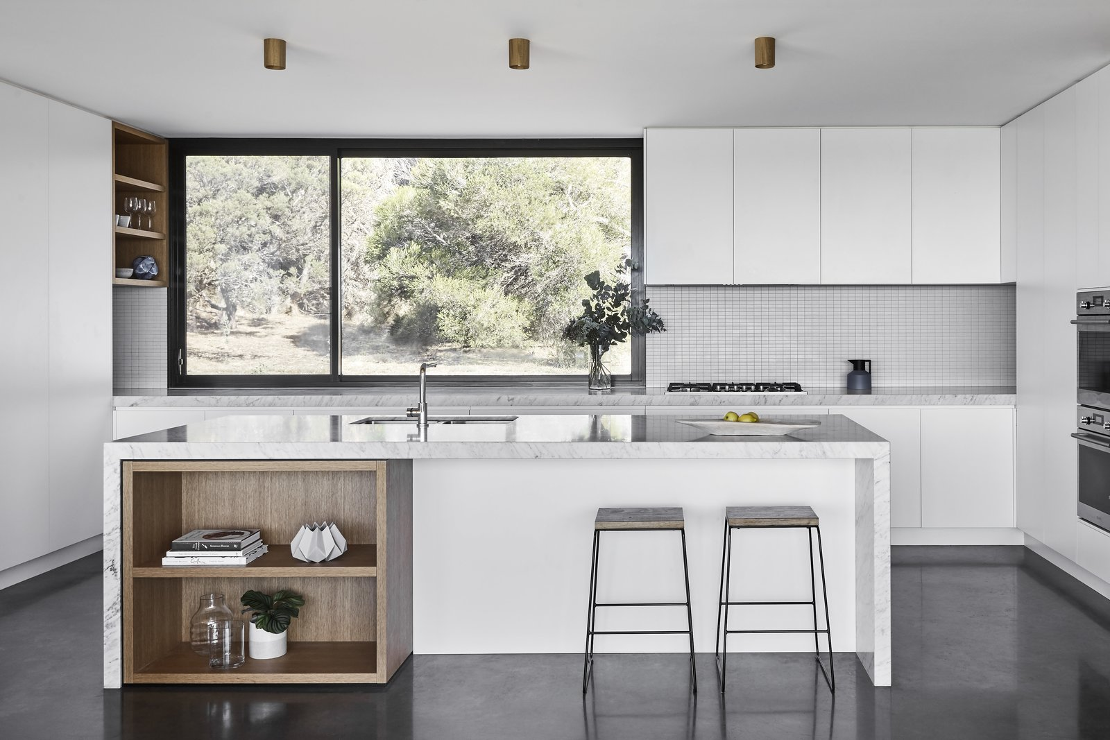 Kitchen, Marble, White, Stone Tile, Wall Oven, Concrete, Cooktops, Ceiling, and Undermount The kitchen features a lovely CDK stone backsplash.    Kitchen Cooktops Undermount Wall Oven Marble White Photos from Two Timber-Clad Pavilions Make Up This Australian Family Retreat
