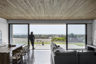 The two pavilions are fitted with large sliding glass doors, which open to two wooden decks. Here, views are oriented toward the peaceful natural landscape and sea beyond.