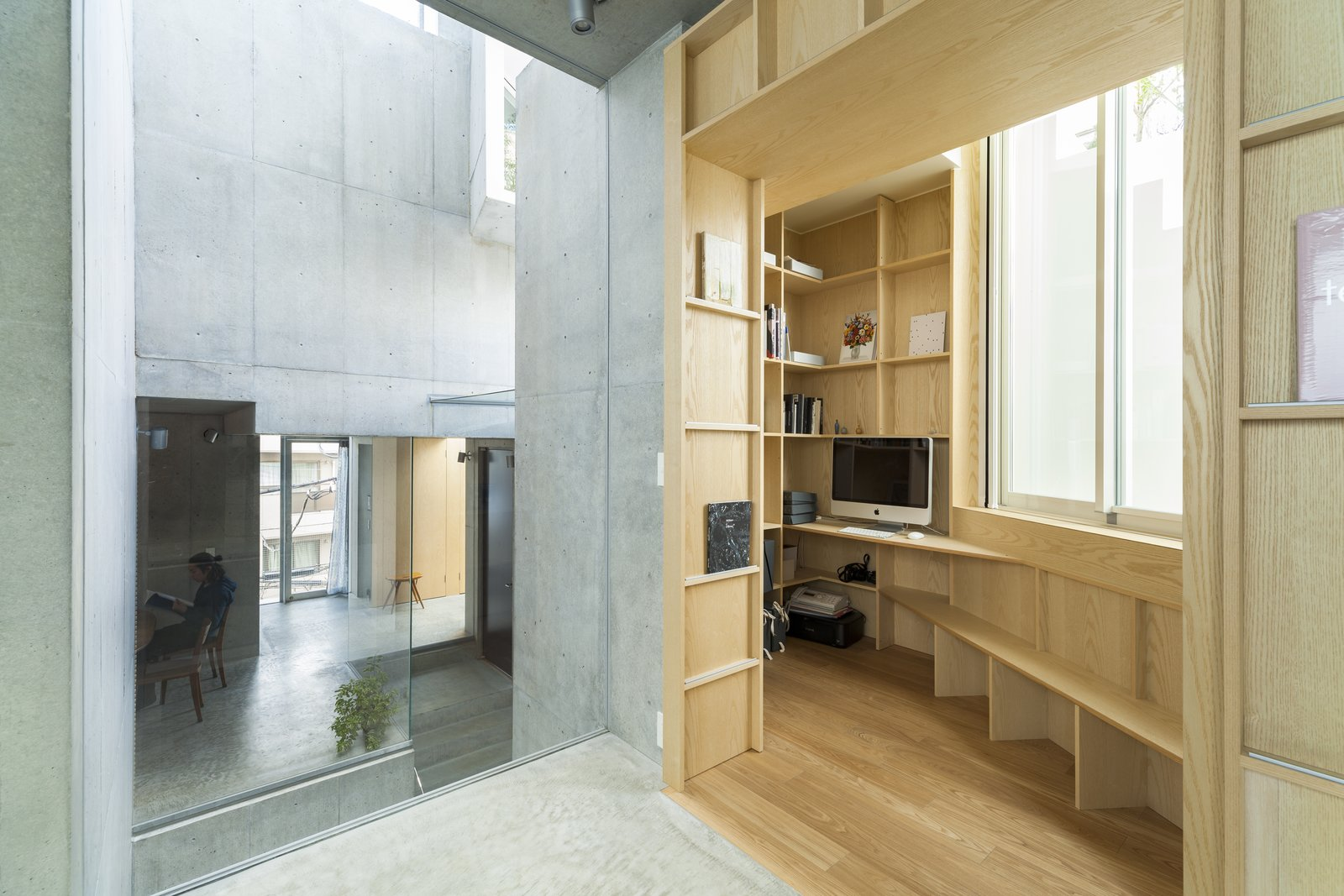 Office, Study Room Type, Bookcase, Desk, and Light Hardwood Floor The living/dining room features large expanses of glass walls. These spaces either look out to the green outdoor areas or into the interior voids.    Best Photos from This Futuristic Japanese Building Is Not Your Everyday Tree House