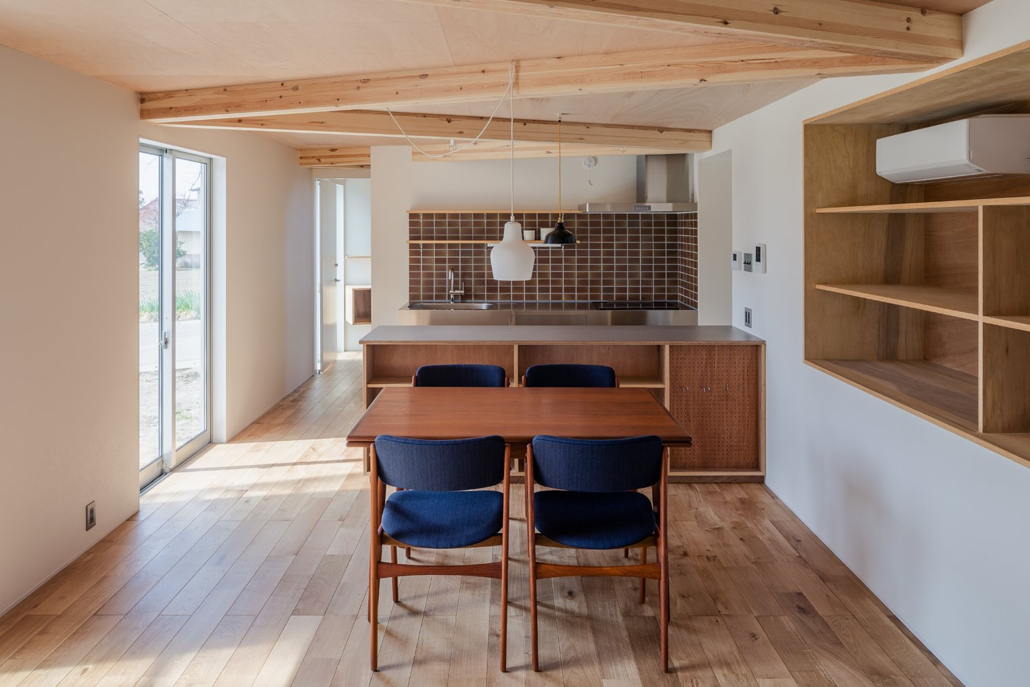 Dining Room, Pendant Lighting, Chair, Light Hardwood Floor, Table, and Shelves Half of the house is a solid volume with a shed roof.   Photos from This Dreamy Japanese Abode Is Part Greenhouse