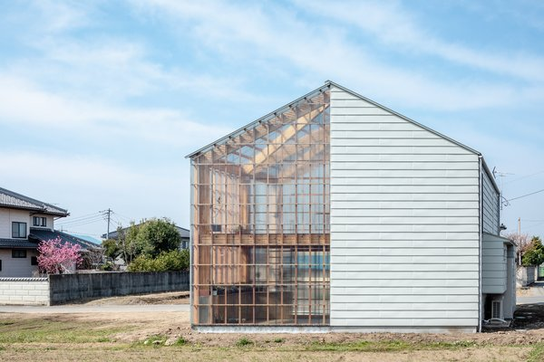 This creates the appearance of a singular gabled house with opaque walls on one side and transparent walls on the other.