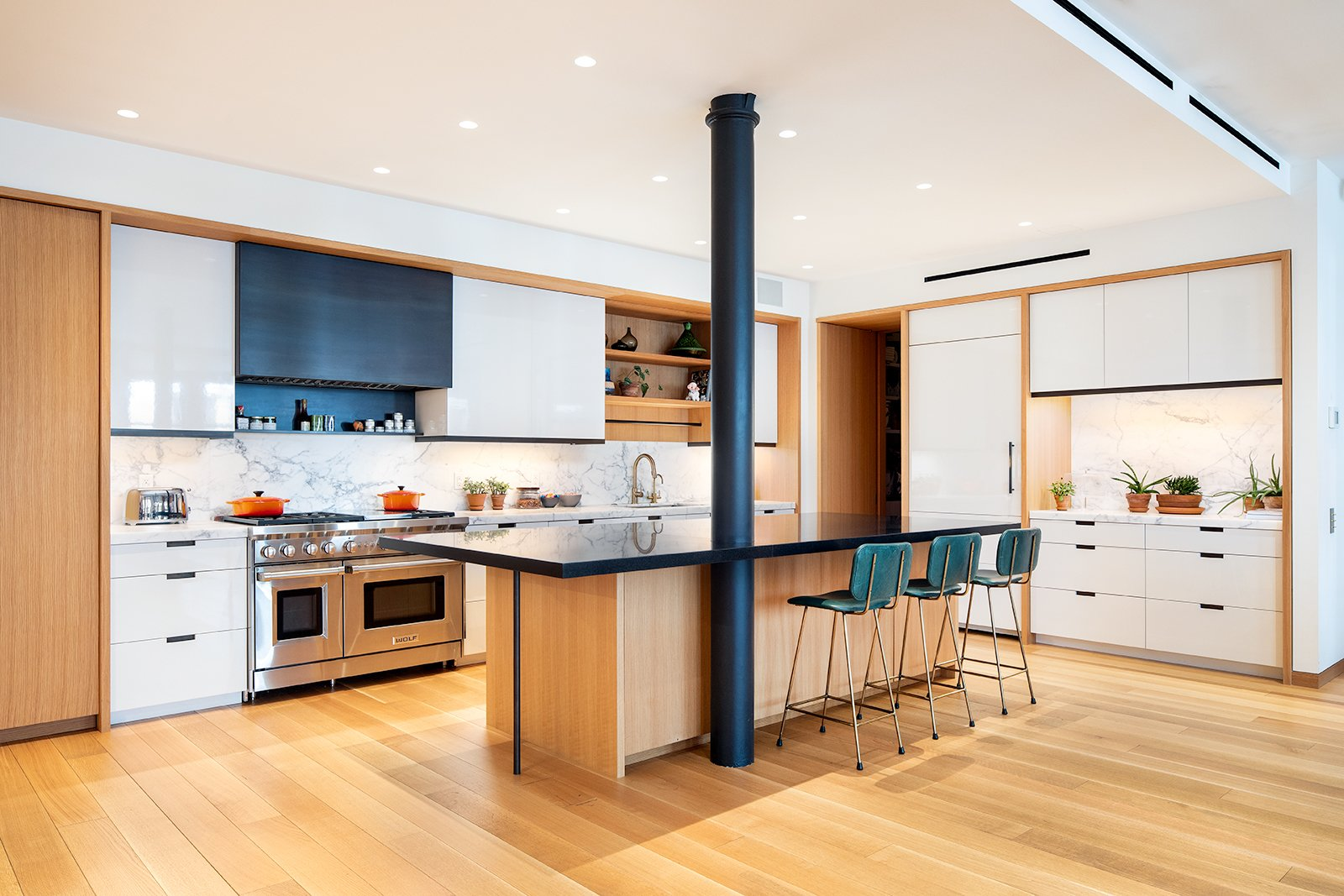 Kitchen, White, Refrigerator, Recessed, Range Hood, Marble, Marble, Granite, Range, Light Hardwood, and Undermount The original cast-iron supporting columns have been painted black to provide a striking contrast to the warm wood.    Best Kitchen Range Hood Light Hardwood Range Refrigerator White Undermount Photos from An Updated Historic Loft in Manhattan Is Listed For $4.5M
