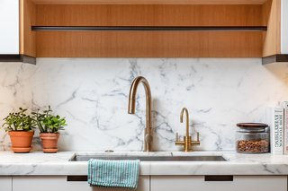 The kitchen features a Calacatta honed marble counter and backsplash, as well as an island with a black granite countertop.