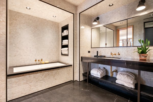 The master bathroom features a custom-designed vanity with bronze legs, a walk-in steam shower, multiple storage cabinets, and oil-rubbed bronze fixtures by Lefroy Brooks.