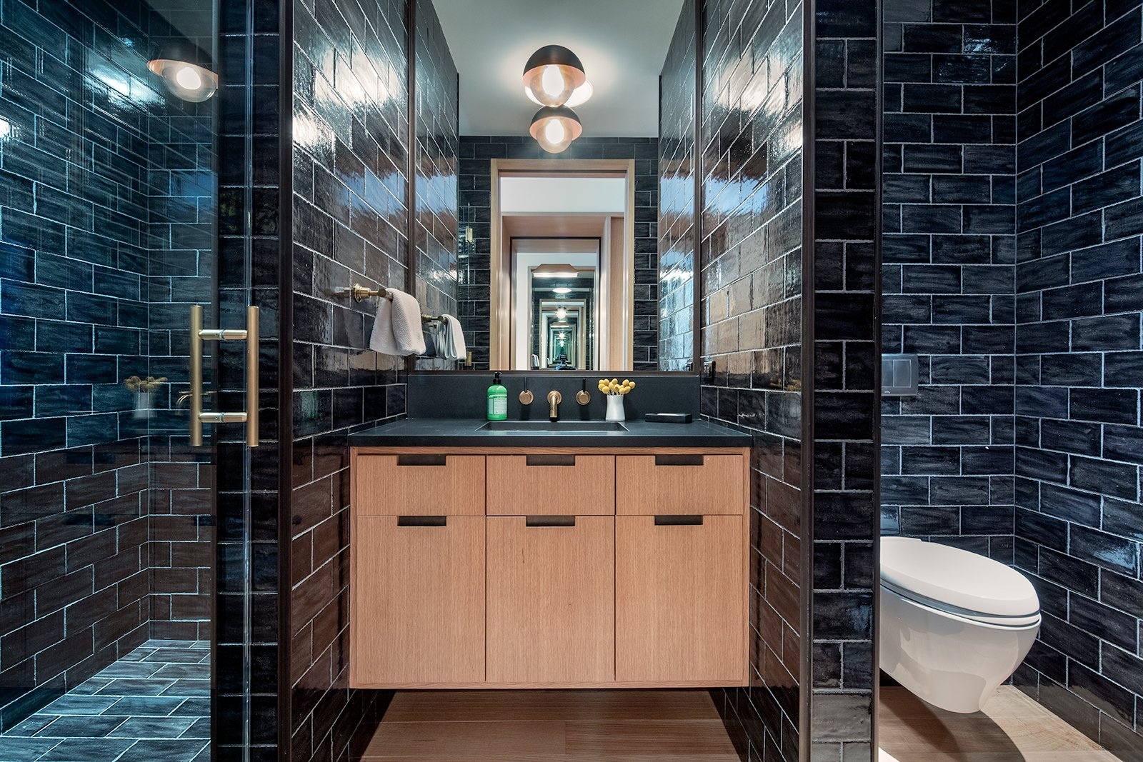 Bath, One Piece, Drop In, Enclosed, Tile, Subway Tile, Light Hardwood, and Wall This bright bedroom has a monochromatic bathroom with a spacious walk-in shower that is covered in sleek subway tiles.      Bath Light Hardwood Tile Photos from An Updated Historic Loft in Manhattan Is Listed For $4.5M