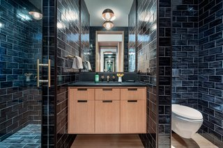 This bright bedroom has a monochromatic bathroom with a spacious walk-in shower that is covered in sleek subway tiles.