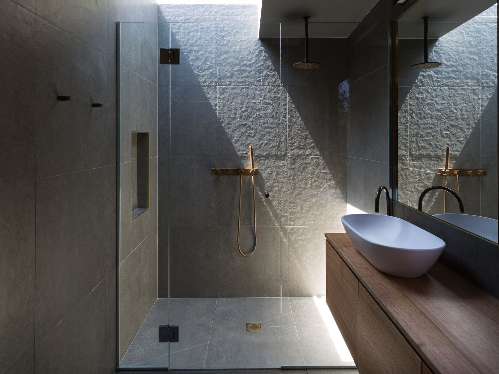 Bath Room, Enclosed Shower, Stone Tile Wall, Wood Counter, and Vessel Sink A skylight brightens the shower area.  Best Photos from A Melbourne Couple Escape City Living in This Tasmanian Retreat
