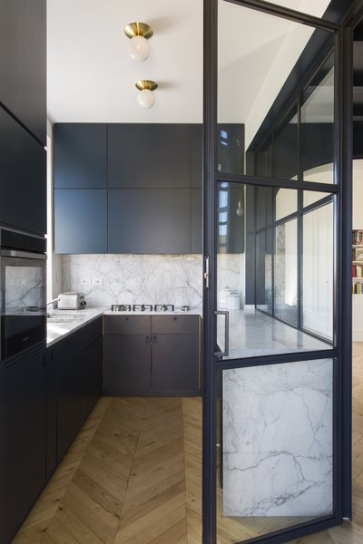 The kitchen of this renovated apartment in Rome dramatically puts a deep veined marble for the counters and backsplash against the dark millwork.
