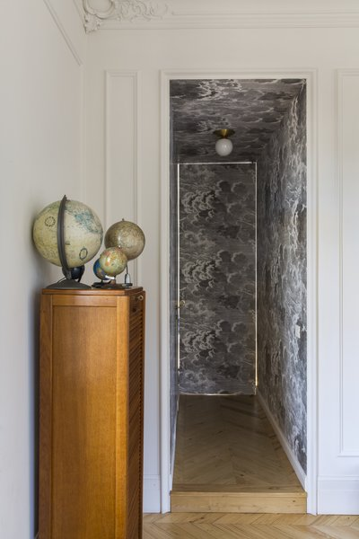 A narrow hallway leads to the bedroom. As you can see, the movement from light colors to dark creates a bold, dramatic aesthetic.