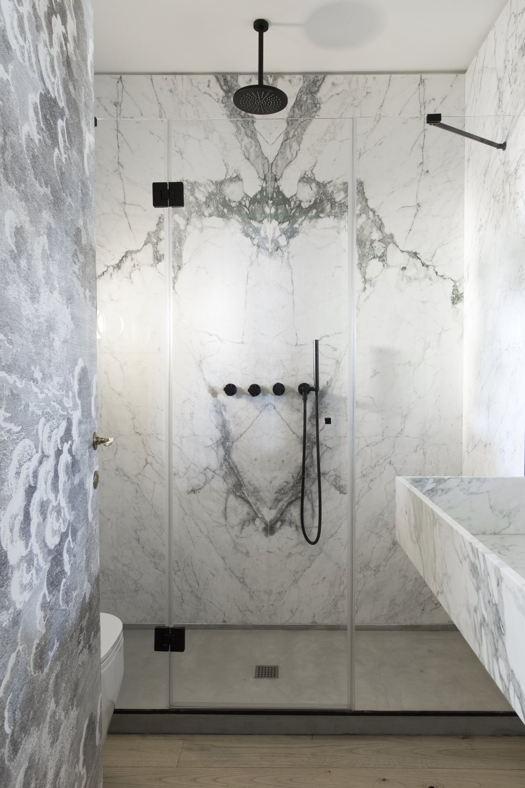 Bath Room, Enclosed Shower, Marble Counter, Marble Wall, Wall Mount Sink, Drop In Sink, and One Piece Toilet The two bathrooms feature gorgeous Carrara marble wall tiles.    Best Photos from A Historic Apartment in Rome Is Treated to a Dramatic New Look