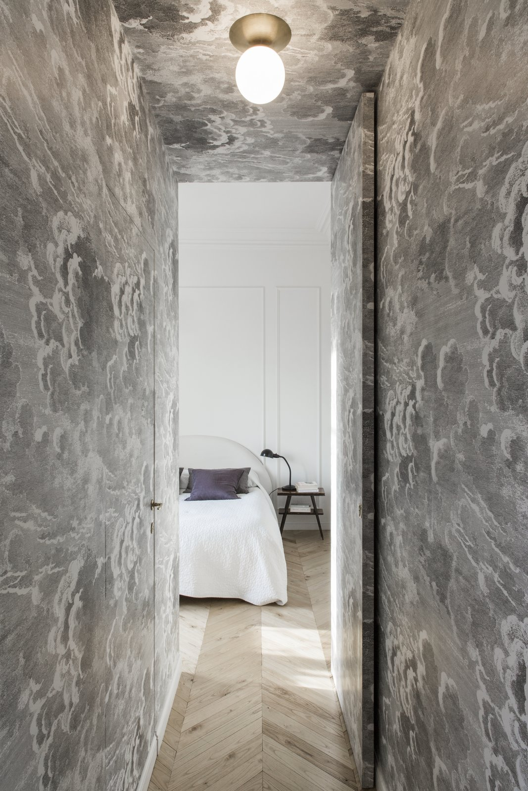 Hallway and Light Hardwood Floor Both the walls of the hallway leading to the master bedroom and the two bathrooms are covered in a Fornasetti wallpaper that features dreamy cloud graphics.     Best Photos from A Historic Apartment in Rome Is Treated to a Dramatic New Look