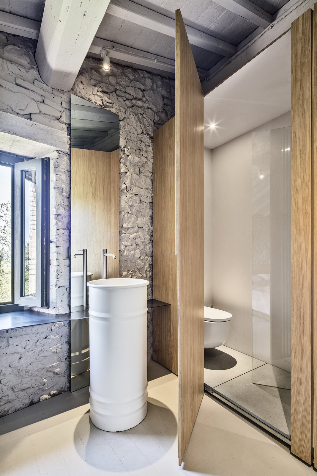 "Bath, Pedestal, Ceiling, One Piece, Concrete, and Painted Wood While using the washbasin, the owner can enjoy outdoor views. ""The 'rarefacted' wooden wall generates a light visual relationship between bedroom and bathroom spaces,"" says Cisi.  Bath Painted Wood Photos from An Old Stone Building in Tuscany Becomes a Modern Hideaway"