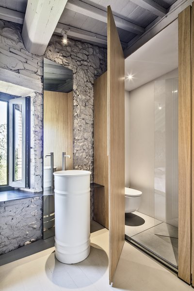"While using the washbasin, the owner can enjoy outdoor views. ""The 'rarefacted' wooden wall generates a light visual relationship between bedroom and bathroom spaces,"" says Cisi."