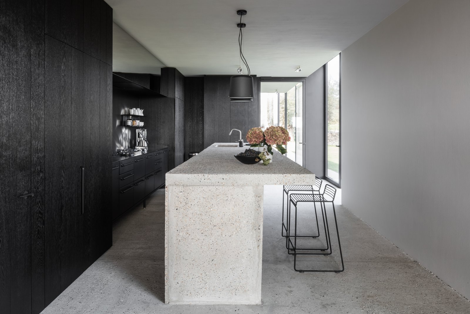 Kitchen, Concrete, Drop In, Pendant, Concrete, Ceiling, and Cooktops The contemporary guest kitchen has been designed and built by Danish brand VIPP.    Best Kitchen Ceiling Concrete Concrete Pendant Photos from An Old Belgian Fortress Breathes New Life as a Charming B&B