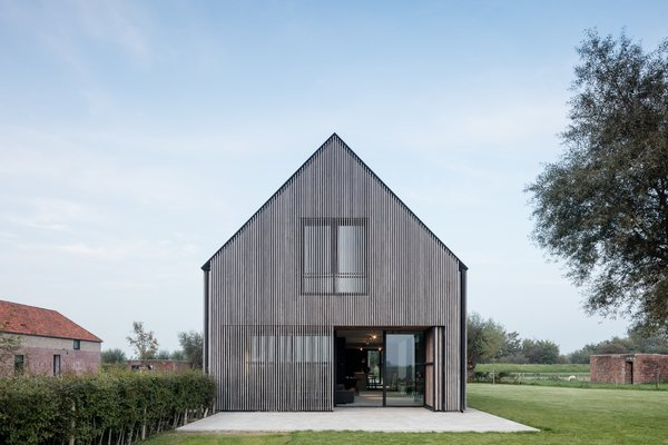 """""""The border between inside and outside fades because of the perpetuation of the washed concrete flooring, reminiscent of cannon bases. Just like the shutters of the old barn, the sliding facades of the expansion offer the opportunity to seal off the guest complex entirely,"""" explains Vanhoutte."""