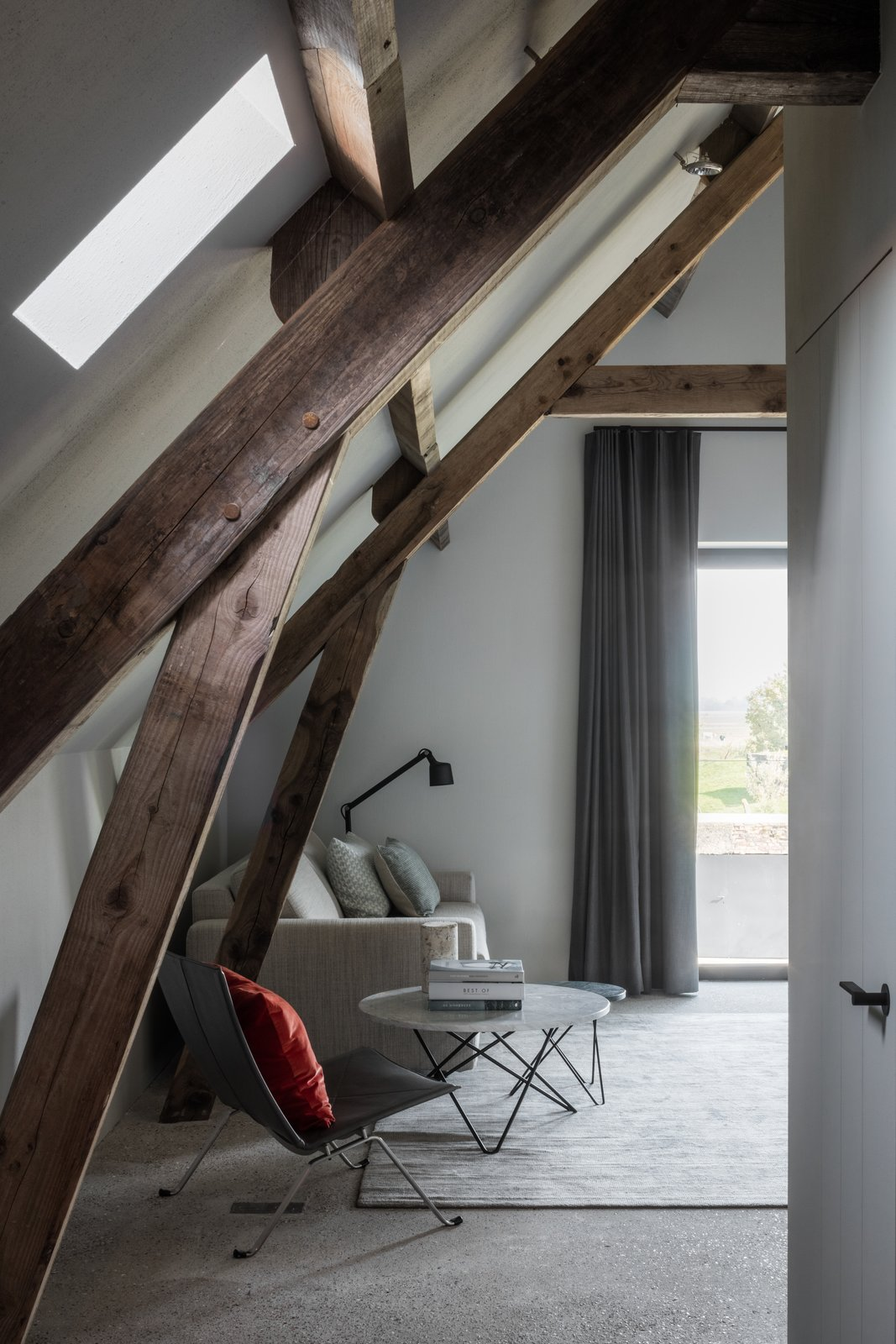 Bedroom, Concrete, Floor, Chair, and Rug Rough, scrubbed concrete and rounder plastering contrast with the restored timber roof beautifully.      Bedroom Concrete Floor Photos from An Old Belgian Fortress Breathes New Life as a Charming B&B