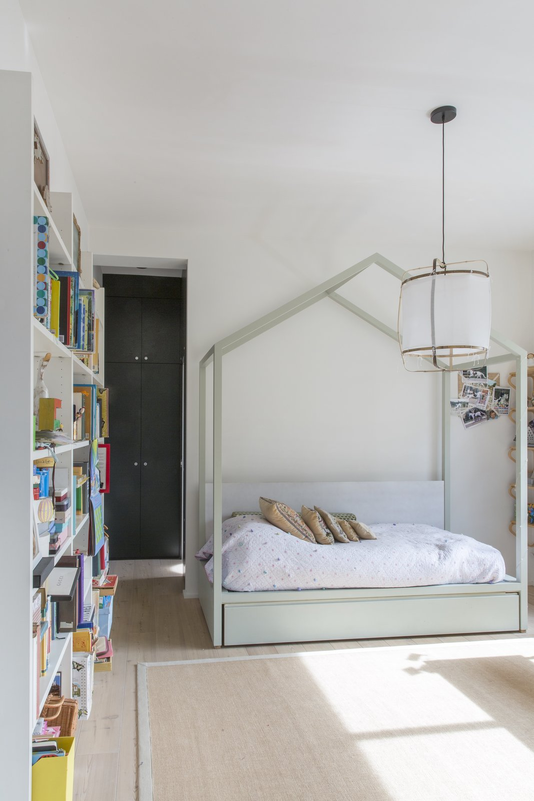 Kids, Bed, Bedroom, Light Hardwood, Rug, and Bookcase A glazed wall forms a corridor that leads toward the daughter's bedroom.    Best Kids Bookcase Bed Light Hardwood Photos from A Pink Staircase Dominates the Revival of This Roman Apartment