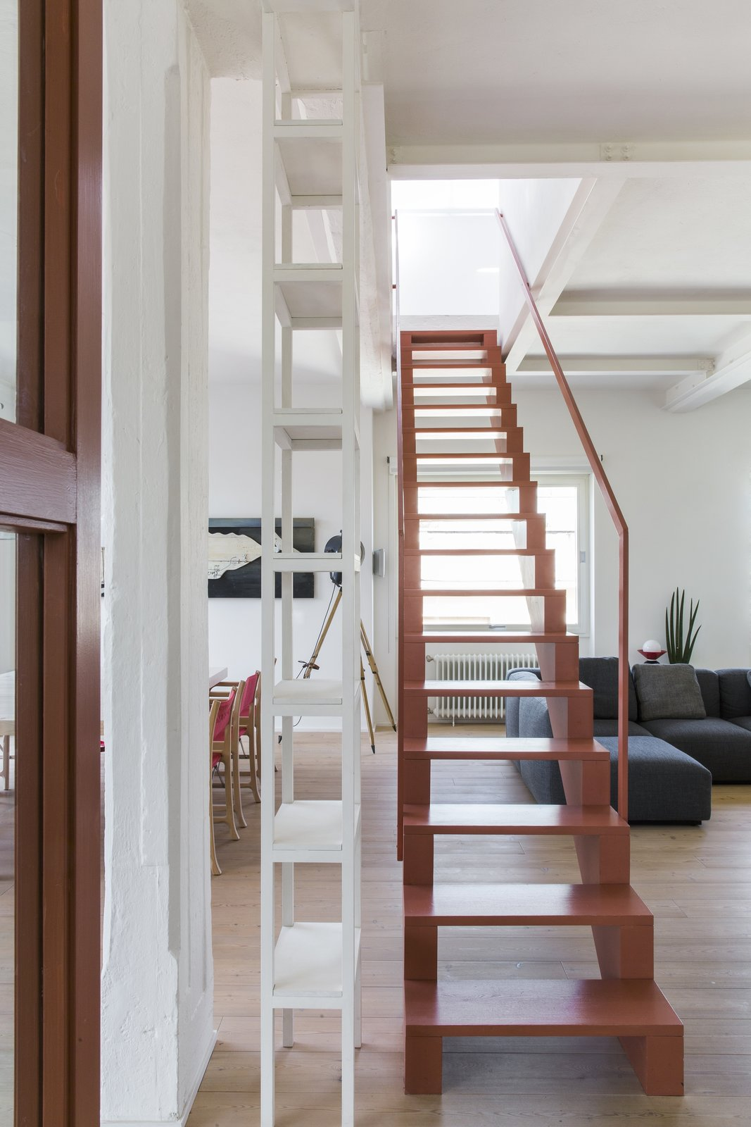 Staircase, Wood Tread, and Wood Railing The pink staircase links the common areas in the lower level with the master bedroom above.    Best Photos from A Pink Staircase Dominates the Revival of This Roman Apartment
