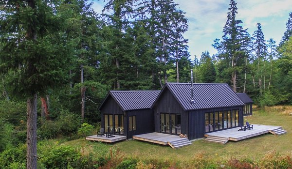 Taking inspiration from the tradition of the Danish sommerhus, each volume is a simple, gabled form, clad in dark gray-stained cedar siding with standing-seam metal roofs that mirror the vertical grooves in a similar shade.