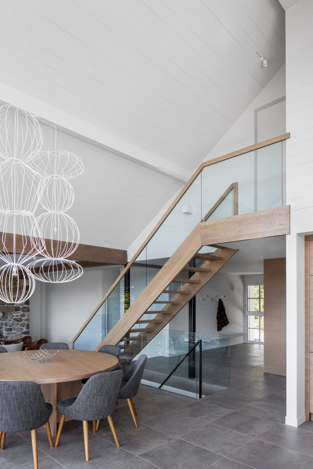 Staircase, Wood Railing, and Wood Tread Hope restyled the interiors to give the property an honest, contemporary feel.     Photo 9 of 13 in A 1960s Canadian Ski House Is Rebuilt Into a Gorgeous Abode