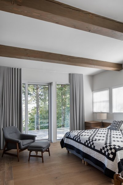 "Four commodious bedrooms were located on the tree-facing side of the house. ""This arrangement also saw that the front door be relocated to create a dramatic reveal through the glass staircase to the valley,"" notes Hope."