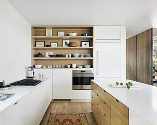 A streamlined modern kitchen with white cabinetry.