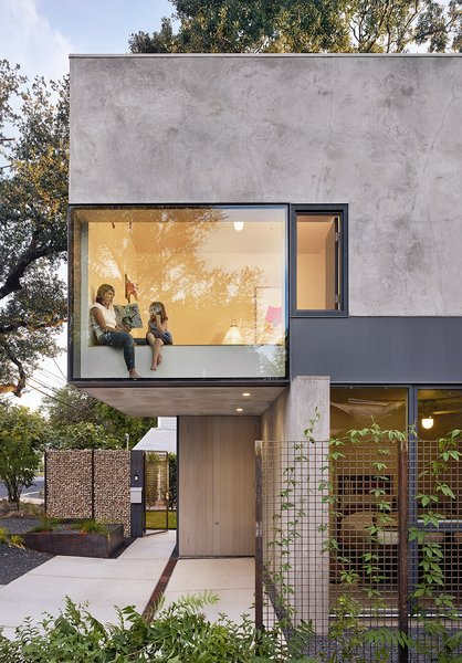 Windows and skylights have been strategically placed throughout to capture striking views of the surrounding trees. Here, a bedroom cantilevers above the entrance patio.