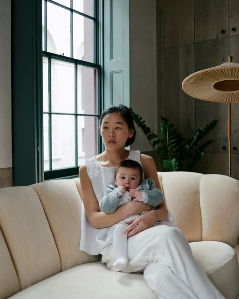 Zoe Chan and her child relax on a Danish banana sofa that Chan + Eayrs reupholstered in Cream Pierre Frey velvet.