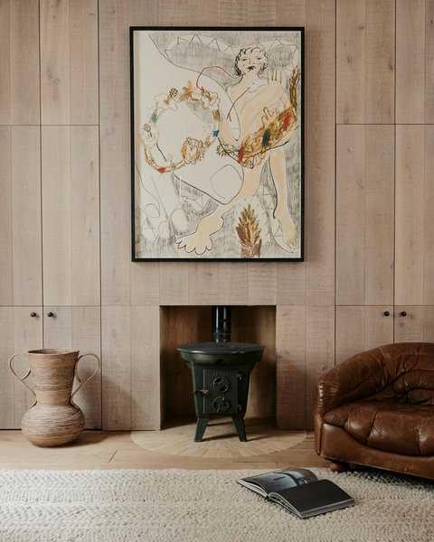 The antique Norwegian log burners in the living room are framed within semicircular hearths made of radial clay bricks.