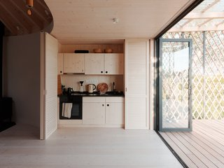 On one side of this large entrance is a kitchen that's concealed by wooden doors and panels when not in use.