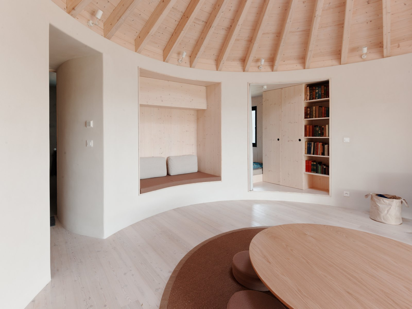 Living Room, Table, Bench, Light Hardwood Floor, Wall Lighting, Rug Floor, and Bookcase From the main room, passageways lead to the bedroom and bathroom.  Photos from This Serene Cabin in Slovakia Takes the Shape of a Yurt
