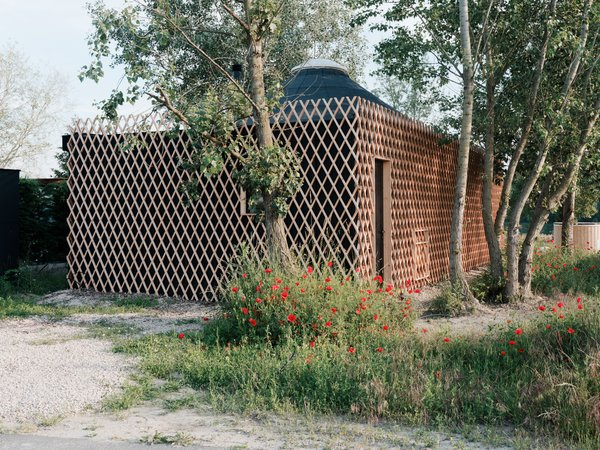 Surrounding the deck at the entrance of the cabin is a lattice-wood frame that serves as a shelter for the outdoor area.