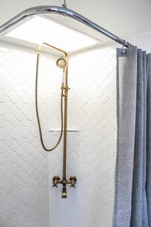 Major alterations were also made in the bathroom. The tired, plastic shower surround was removed and replaced with beautiful scalloped tiles from Floor & Décor, and a gold-colored shower head, purchased from Amazon, adorns the compact shower area. A ceiling-mounted shower rod and Target shower curtain replaced the heavy, dated shower doors that existed.