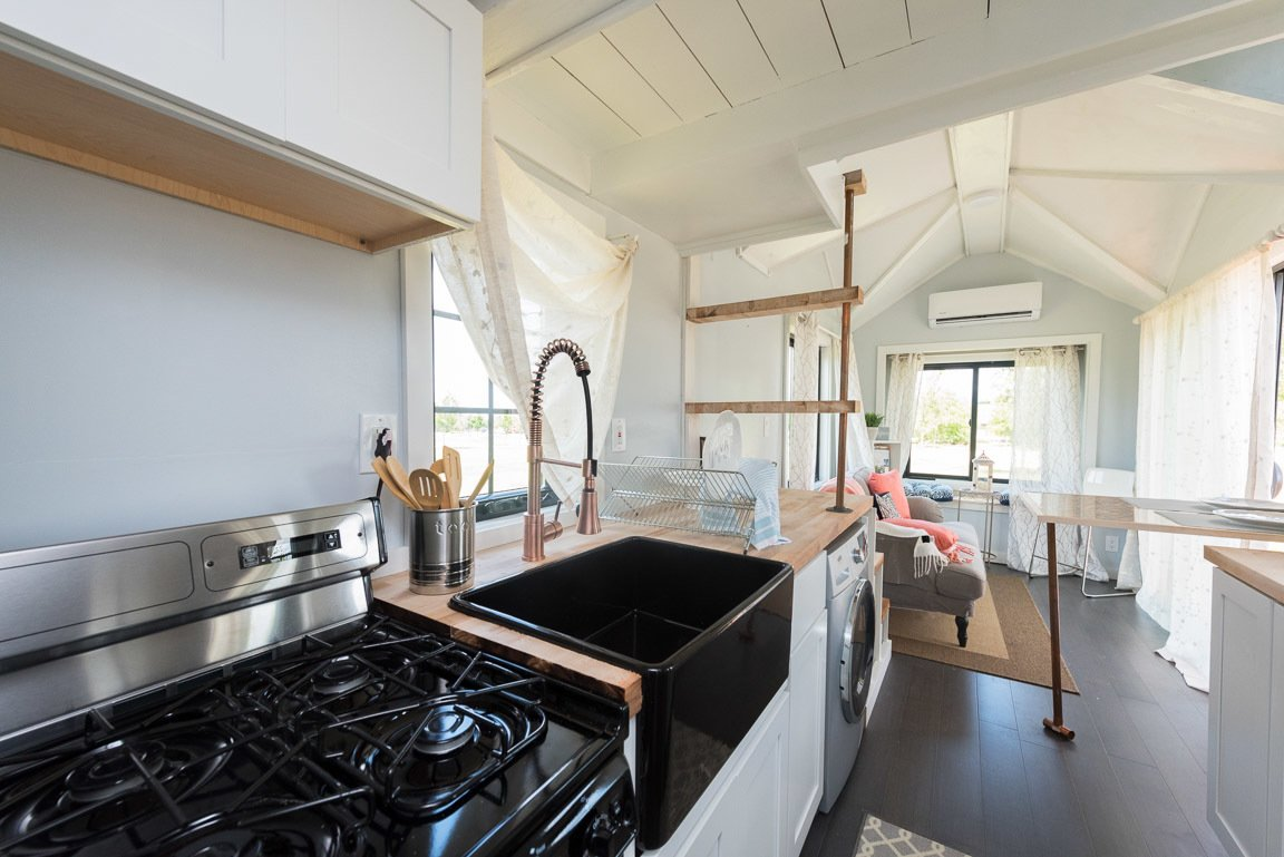 Kitchen, White Cabinet, Drop In Sink, Range, and Wood Counter The tiny house comes with a fully equipped kitchen.  Photo 10 of 11 in This Svelte Tiny Home Is Being Auctioned For Charity