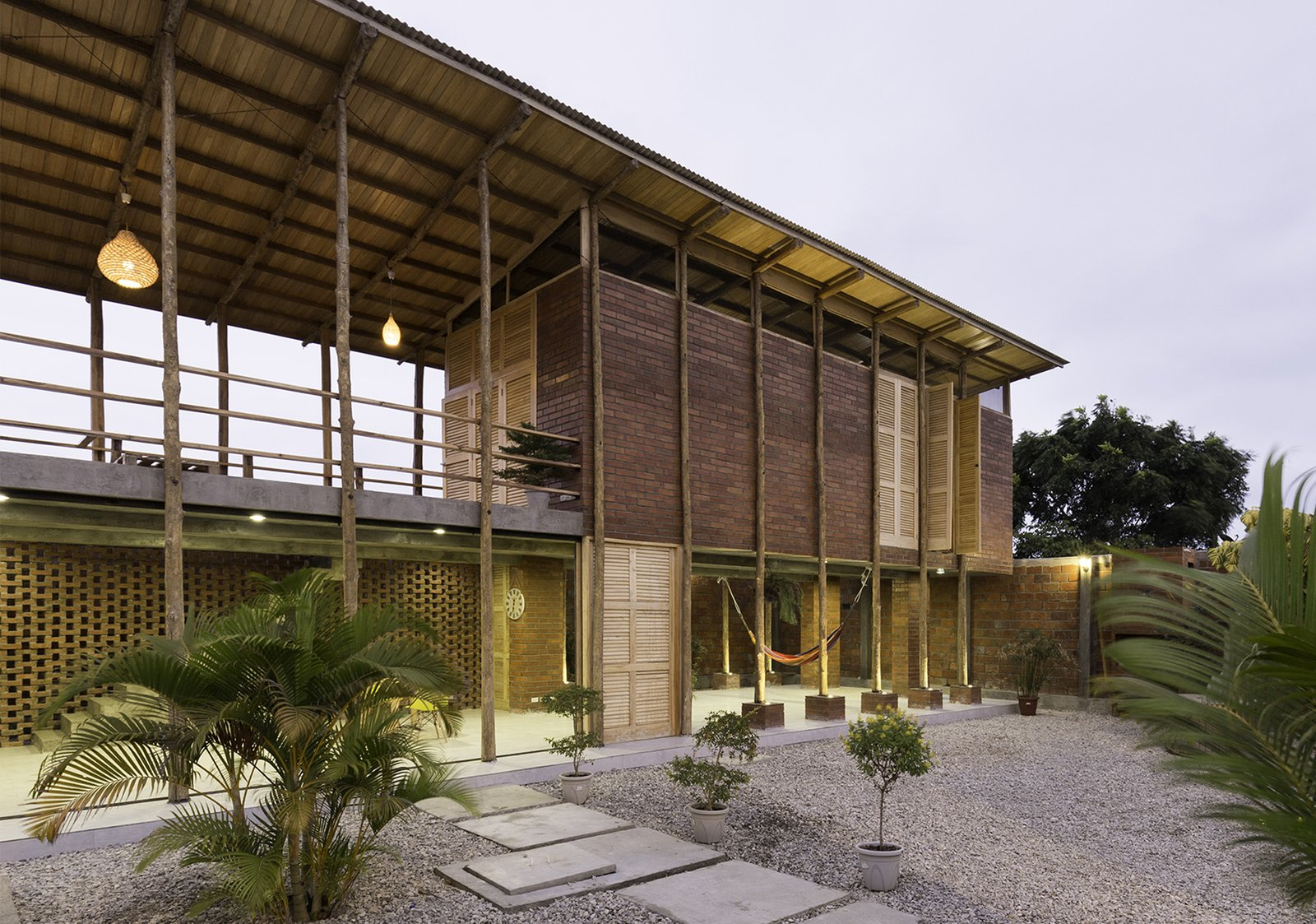 Exterior, Metal Roof Material, Shed RoofLine, House Building Type, Brick Siding Material, Wood Siding Material, and Beach House Building Type As its name suggests, the house rests upon wooden stilts, which passively cools the interiors.  Photo 2 of 16 in Beach Breezes Blow Right Through This Ecuadorian House on Stilts