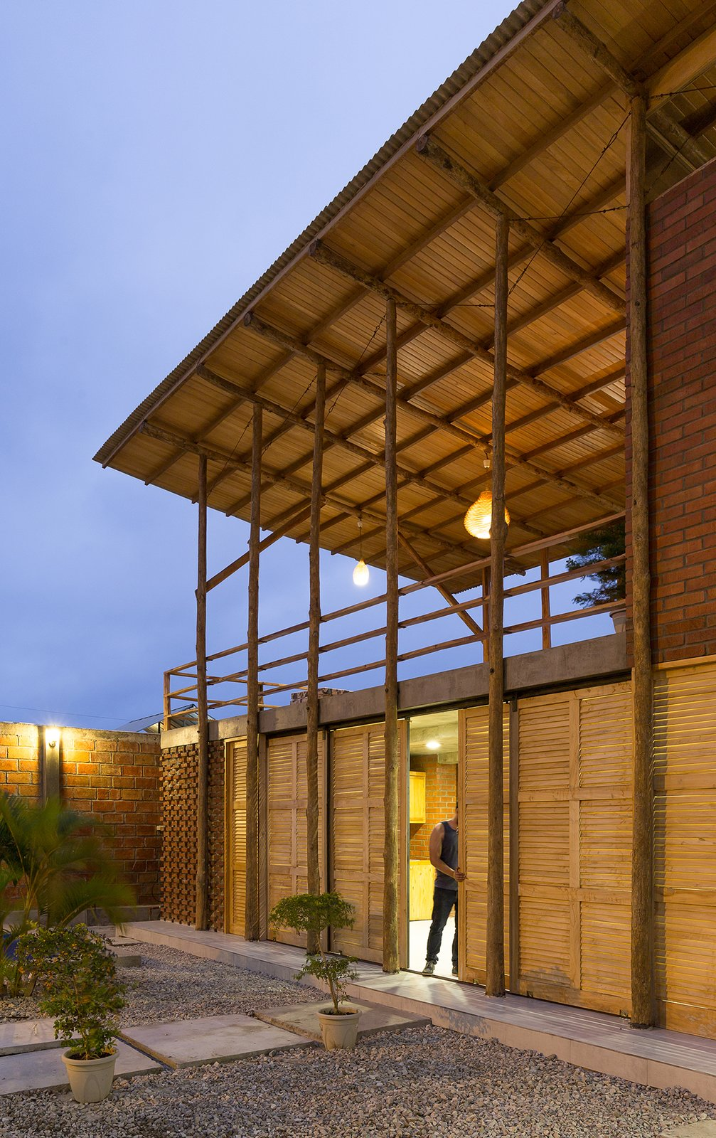 Exterior, Brick Siding Material, Metal Roof Material, Wood Siding Material, Shed RoofLine, House Building Type, and Beach House Building Type The communal area is fitted with wooden sliding doors, which open to connect the space seamlessly with the surrounding garden.    Photo 11 of 16 in Beach Breezes Blow Right Through This Ecuadorian House on Stilts