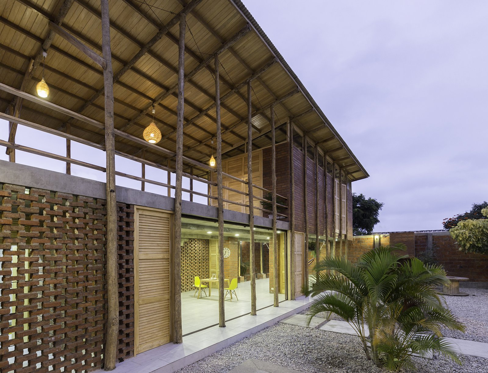 Exterior, Brick Siding Material, Metal Roof Material, Shed RoofLine, House Building Type, Wood Siding Material, and Beach House Building Type On one side of the ground floor is a communal area, enclosed on two sides with brick walls.   Photo 9 of 16 in Beach Breezes Blow Right Through This Ecuadorian House on Stilts