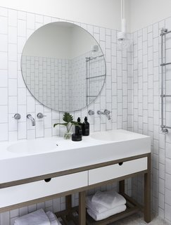 Subway tiles have been laid in a vertical pattern in the bathroom to echo the height of the palm trees just outside this area.