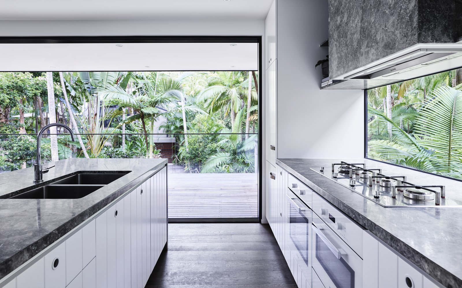 Kitchen, Cooktops, Wall Oven, Recessed Lighting, White Cabinet, Light Hardwood Floor, and Undermount Sink A spacious balcony has been added to the residence.  Photo 7 of 17 in Reconnect With Nature at This Revamped Rainforest Retreat