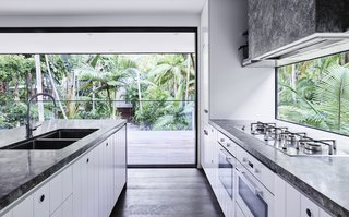 Marble countertops of black and white with kitchen cabinets finished in sparkling white are offset by a unique glass backsplash, which offers a hint of the surrounding rainforest.
