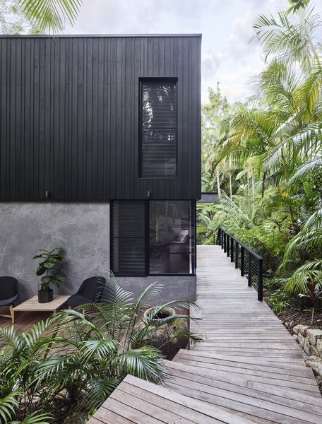 On one side of the home is a boardwalk that runs alongside verdant tropical plants. This boardwalk takes residence from the interior of the house, and goes out to the rainforest.