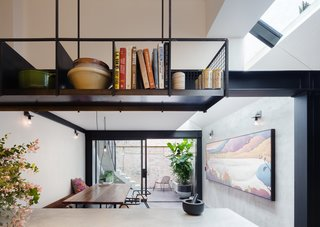 Behind the library wall, and beyond the switchback staircase is a kitchen and dining area that opens out to a streamlined courtyard with herringbone brickwork floor.